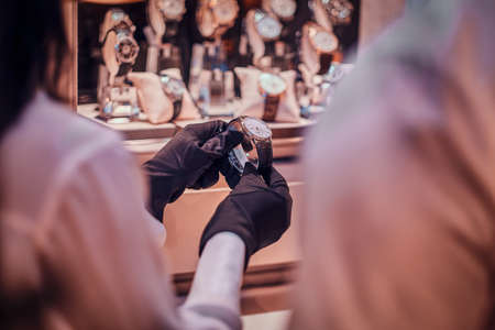 Photo for Shop assistant in black gloves is showing expensive watch for a customer. - Royalty Free Image