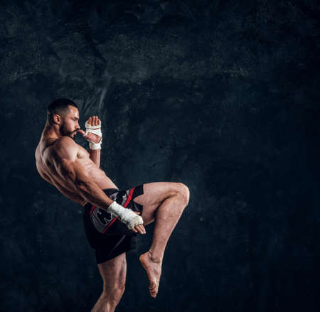 Photo pour Muscular handsome fighter with naked torso is demonstraiting his power at dark photo studio. - image libre de droit