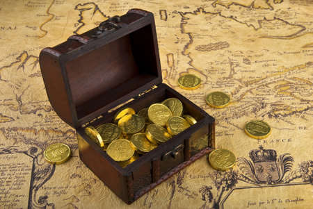 Very old map with treasure chest full of golden coins on a vintage map