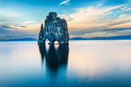 Foto per Hvitserkur is a spectacular rock in the sea on the Northern coast of Iceland. Legends say it is a petrified troll. On this photo Hvitserkur reflects in the sea water after the midnight sunset.  - Immagine Royalty Free