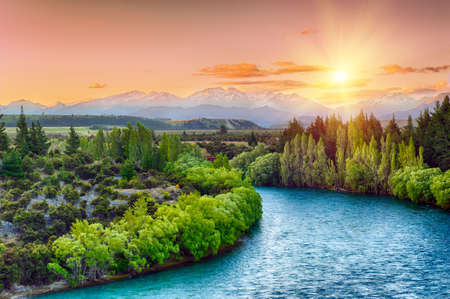 Photo pour Beautiful sunset over the bend of the river Clutha with Southern Alps peaks on the horizon, New Zealand - image libre de droit