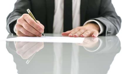 Foto de Cropped view of lawyer sitting at white desk signing legal document.  - Imagen libre de derechos