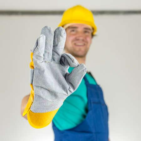 Foto de Closeup of young construction worker showing ok hand sign  - Imagen libre de derechos