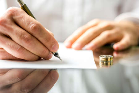 Photo for  Closeup of a man signing  divorce papers.  - Royalty Free Image