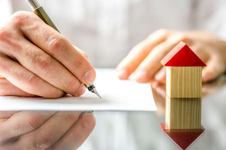 Foto de Conceptual image of a man signing a mortgage or insurance contract or the deed of sale when buying a new house or selling his existing one with a small wooden model of a house alongside - Imagen libre de derechos