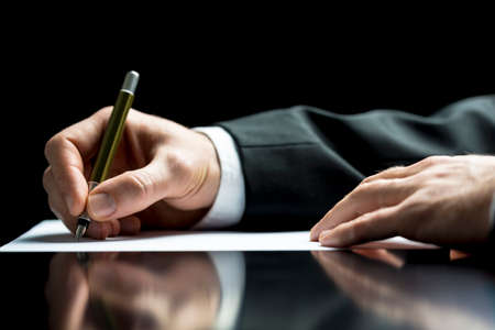 Photo for Businessman writing a letter, notes or correspondence or signing a document or agreement, close up view of his hand and the paper - Royalty Free Image