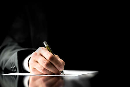 Photo pour Businessman signing a document, taking notes, completing a questionnaire or writing correspondence, close up view of his hand and the paper - image libre de droit