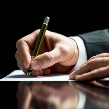 Foto de Businessman writing on a sheet of white paper with a fountain pen as he signs an agreement or contract, writes correspondence, takes notes or completes a questionnaire, closeup low angle view - Imagen libre de derechos