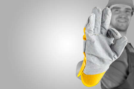 Photo pour Workman making a perfect gesture with his gloved hand with focus to his hand over a grey background with a highlight and copyspace. - image libre de droit