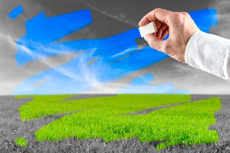 Foto de Conceptual image of a man erasing pollution as he rubs over a greyscale landscape to reveal the green grass and blue sky beneath. - Imagen libre de derechos