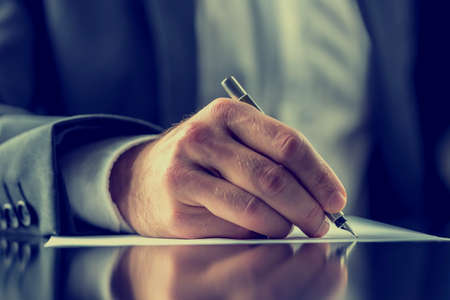 Photo for Man signing a document or writing correspondence with a close up view of his hand with the pen and sheet of notepaper on a desk top. With retro filter effect. - Royalty Free Image