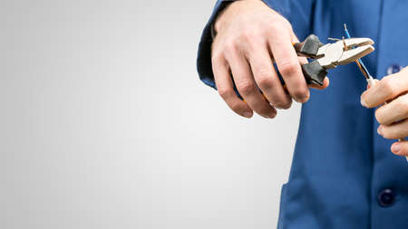 Foto de Workman or electrician repairing an electrical cable with a pair of pliers to restore supply to the house, close up view of his hands in blue overalls on grey with copyspace - Imagen libre de derechos