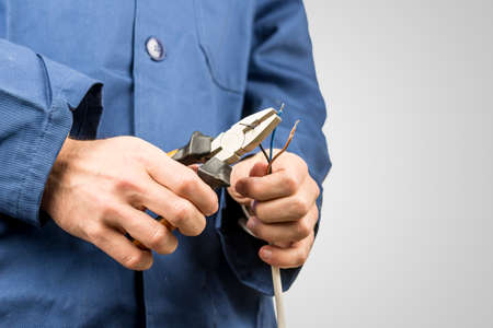 Foto de Workman repairing an electrical cable with a pair of pliers. On grey background with copyspace. - Imagen libre de derechos