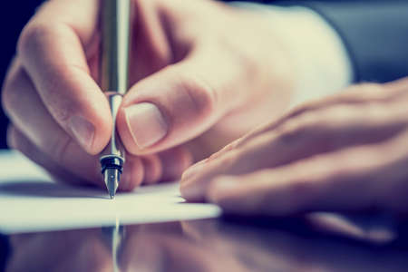 Photo for Retro effect faded and toned image of a man writing a note with a fountain pen. - Royalty Free Image