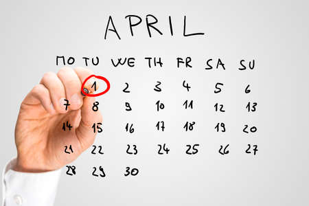 Photo for Hand drawn calendar for April on a virtual interface or screen with the First ringed in red by a man holding a marker pen, closeup of his hand. Fools day concept. - Royalty Free Image