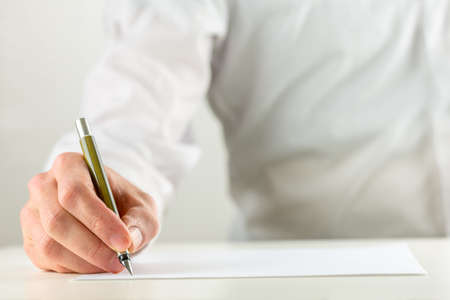 Foto de Close up of the hand of a man writing with a fountain pen on a sheet of blank white paper or document in a conceptual image. - Imagen libre de derechos