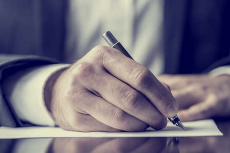 Photo pour Man signing a document or writing correspondence with a close up view of his hand with the pen and sheet of notepaper on a desk top. With retro filter effect. - image libre de droit