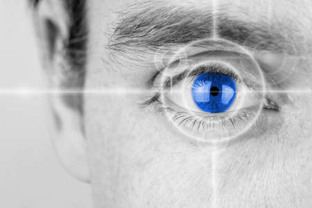 Photo pour Vision concept with a greyscale image of a mans eye with a crosshair focused on his iris which has been selectively colored blue. - image libre de droit
