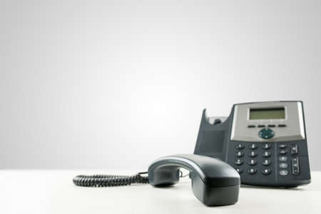 Photo pour Close-up of a black business landline telephone with the receiver off-hook, on an empty desk, with copy space on the grey background. Conceptual of customer service or customer support. - image libre de droit