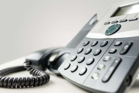 Photo pour Close up angled view of a landline telephone instrument with a number pad and the handset or receiver off the hook in a communications concept. - image libre de droit