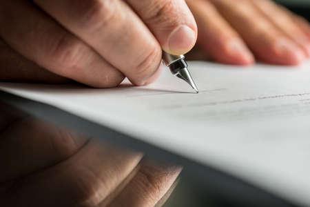 Foto de Closeup of male hand about to sign a business contract with a fountain pen.  - Imagen libre de derechos