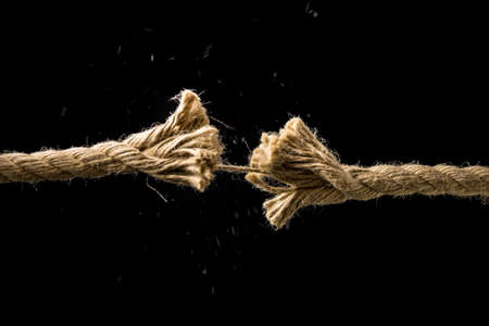 Photo pour Concept of danger and risk with two ends of a frayed worn rope held together by the last strand on the point of snapping, against a dark background with copyspace. - image libre de droit
