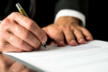 Photo pour Close up of the hands of a businessman signing a typed document with a fountain pen with copyspace in the foreground. - image libre de droit