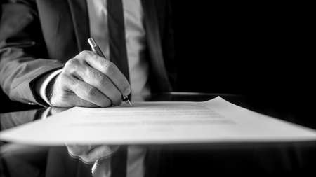 Photo for Black and white low angle image of the hand of a businessman in a suit signing a document or contract with a fountain pen on a reflective surface  - Royalty Free Image