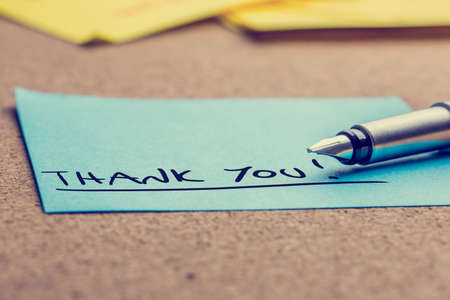 Foto für Handwritten Thank You note written on a blue sticky note lying on a cork board with a fountain pen viewed low angle. - Lizenzfreies Bild
