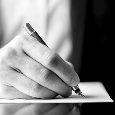 Photo pour Low angle black and white image of a male hand holding a fountain pen as though writing on a blank sheet of paper with shallow dof in square format. - image libre de droit