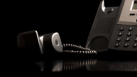 Photo pour Telephone handset off the hook lying on a black reflective surface alongside the instrument , close up low angle view with copyspace. - image libre de droit