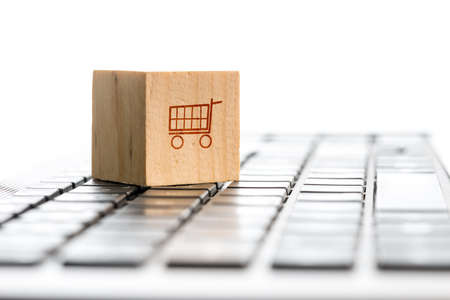 Foto de Online shopping and e-commerce concept with a wooden block with an icon of a shopping cart standing on a computer keyboard, viewed low angle with copyspace. - Imagen libre de derechos
