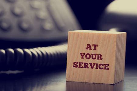 Foto de At Your Service written on a wooden cube in front of a telephone conceptual of help, client services, assistance, expertise and consultancy. - Imagen libre de derechos
