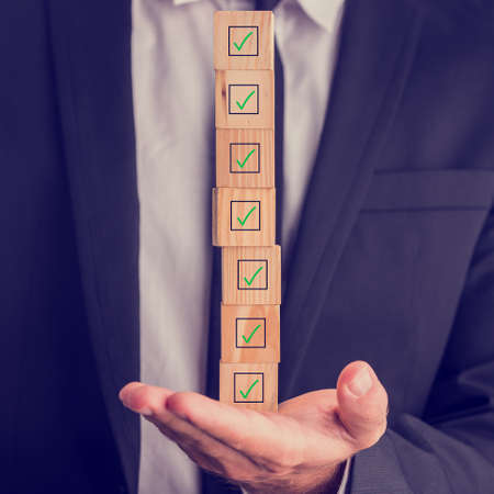 Photo pour Businessman holding a stack of checked boxes marked on wooden cubes balanced on his hand conceptual of quality, completion, approval or voting. - image libre de droit