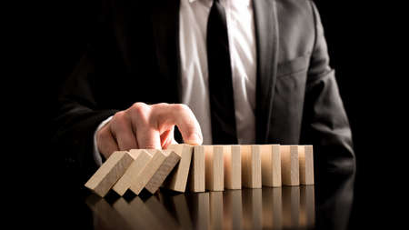 Photo pour Businessman Stopping the Domino Effect from Small Wooden Blocks on the Table. A Creative Concept for Solution to Problem. - image libre de droit