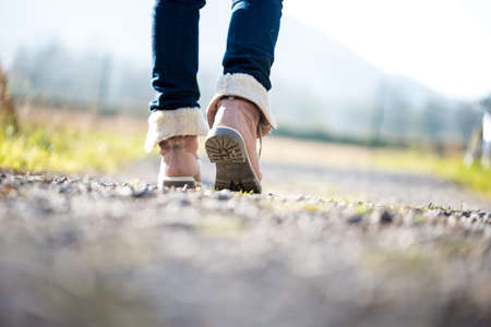 Photo pour Low angle ground level view with shallow dof of the feet of a woman in jeans and ankle high leather boots walking along a rural path away from the camera. - image libre de droit