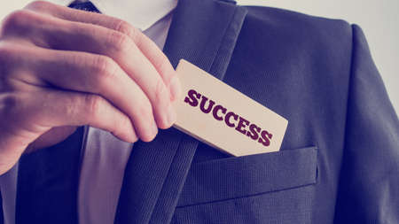 Foto de Successful businessman showing a wooden card reading - Success - as he withdraws it from the pocket of his suit jacket, close up of his hand with retro faded filter effect. - Imagen libre de derechos
