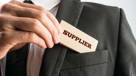 Foto de Businessman showing a wooden card reading - Supplier - as he withdraws it from the pocket of his suit jacket. - Imagen libre de derechos