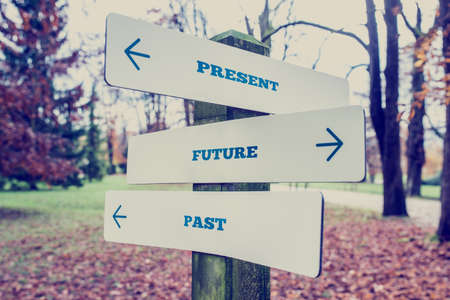 Photo pour Conceptual Design of Present, Future and Past on Direction Sign Board on a Grassy Landscape with Trees at the Background. - image libre de droit