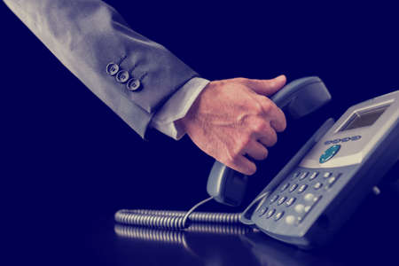 Photo pour Retro image of businessman making a phone call holding the handset receiver of a telephone in his hand , close up view of his hand in a suit. - image libre de droit
