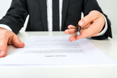Photo pour Front view of a businessman offering you to sign a document with focus to the text Terms and Conditions. - image libre de droit