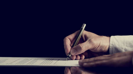 Photo pour Retro image of a man signing a contract over dark background. - image libre de droit