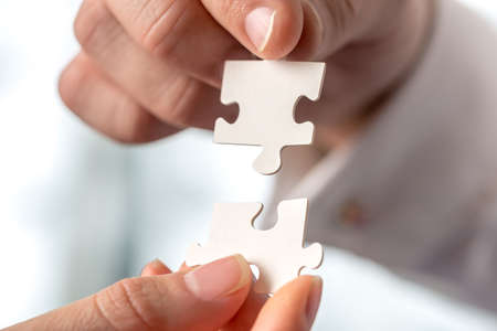 Foto de Two businesspeople fitting together matching interlocking puzzle pieces conceptual of teamwork and problem solving, closeup of their hands. - Imagen libre de derechos