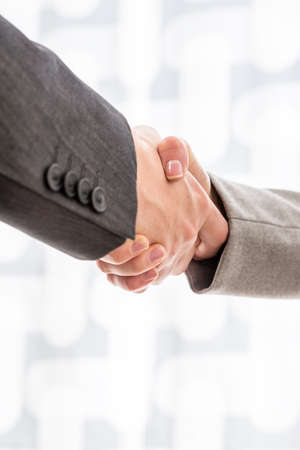 Close up view of the arms of two businesspeople in suits shaking hands over a blurred abstract background conceptual of a deal, agreement, partners or greeting, vertical format with copyspace.