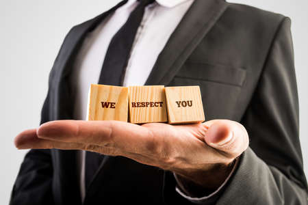 Photo for Businessman holding three wooden cubes or building blocks in the palm of his hand with the words - We respect you - in a conceptual image. - Royalty Free Image