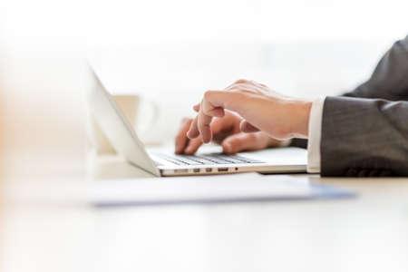 Foto de Closeup of lawyers hands typing legal document on laptop computer. - Imagen libre de derechos