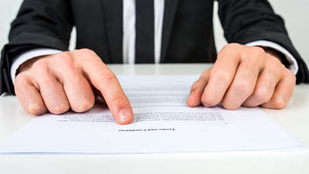 Photo pour Closeup of a lawyer or a real estate agent proofreading Terms and conditions document. - image libre de droit