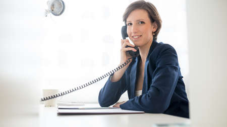 Photo pour Friendly attractive young businesswoman talking on the telephone as she sits at her desk in the office turning to smile at the camera. - image libre de droit