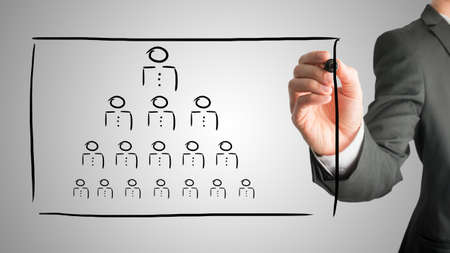 Photo for Businessman drawing a hierarchy concept on a virtual interface with a pyramid formation of people depicting the boss, leadership and work force in human resources. - Royalty Free Image