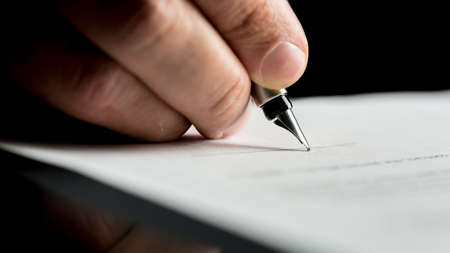 Photo pour Macro shot of a hand of a businessman signing or writing a document on a sheet of white paper using a nibbed fountain pen. - image libre de droit